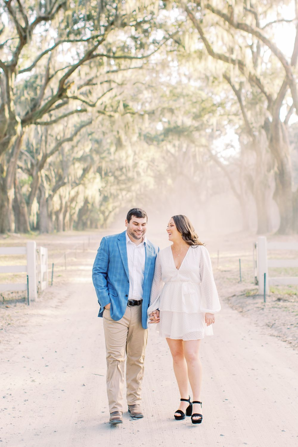 couple holds hands while laughing and walking in the middle of the road at wormsloe state historic park in savannah, ga
