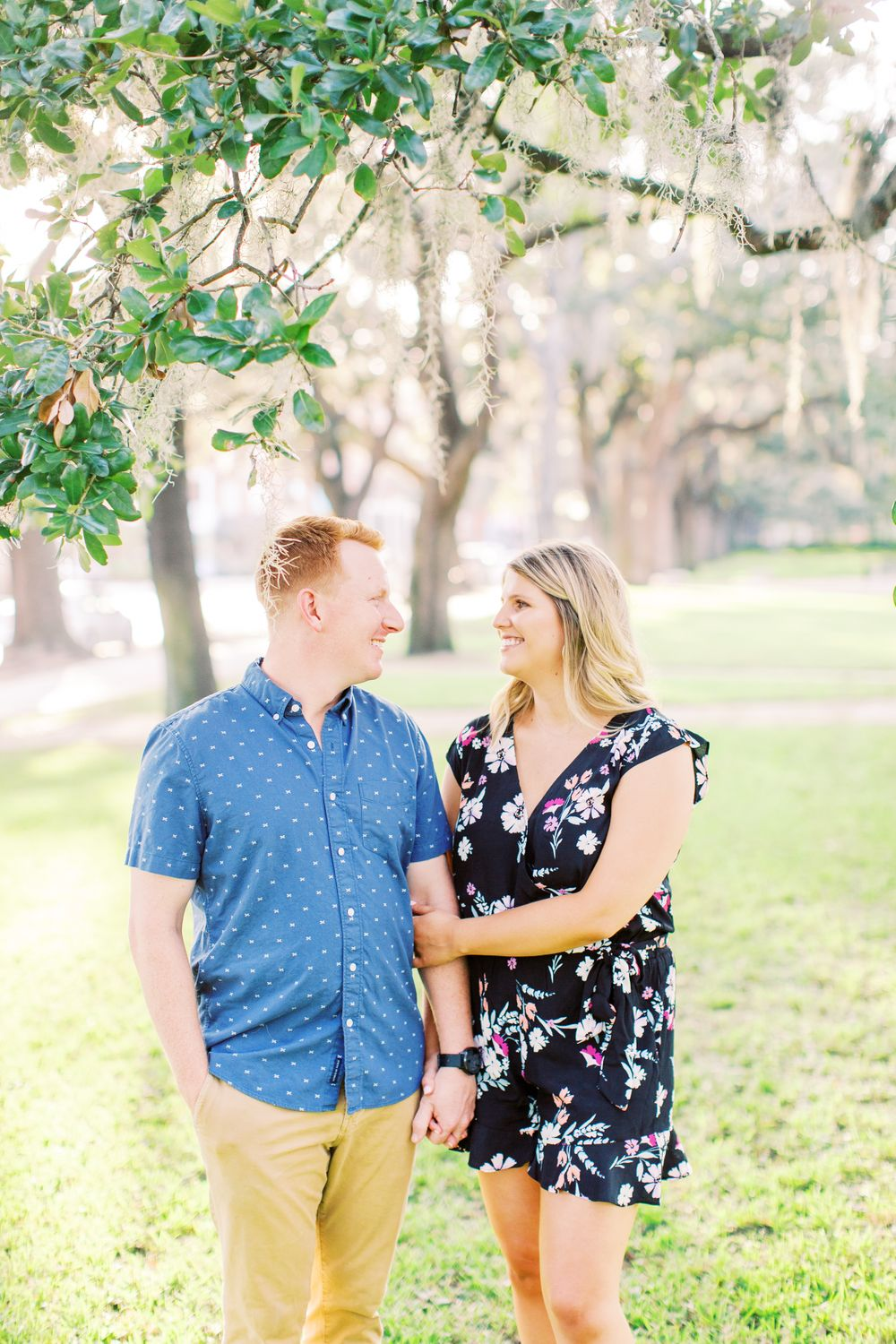 couple smiles at each other during downtown savannah engagement session