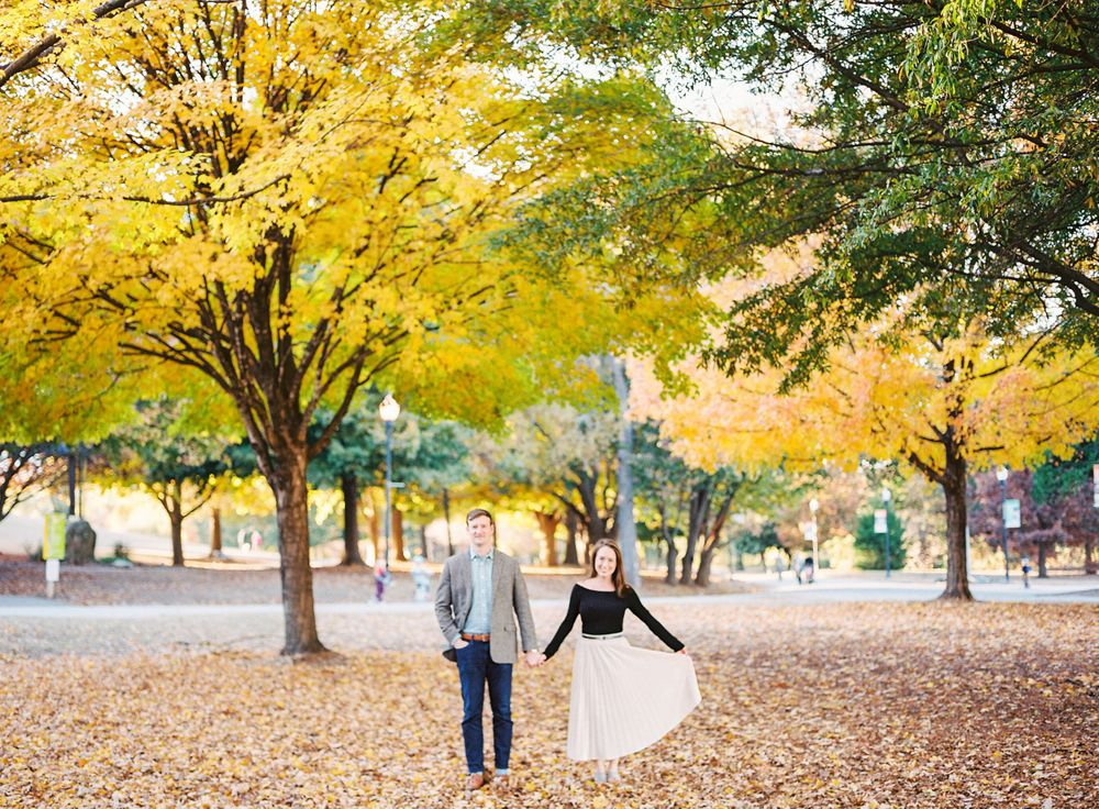 couple enjoy the fall leaves in piedmont park of downtown atlanta, ga