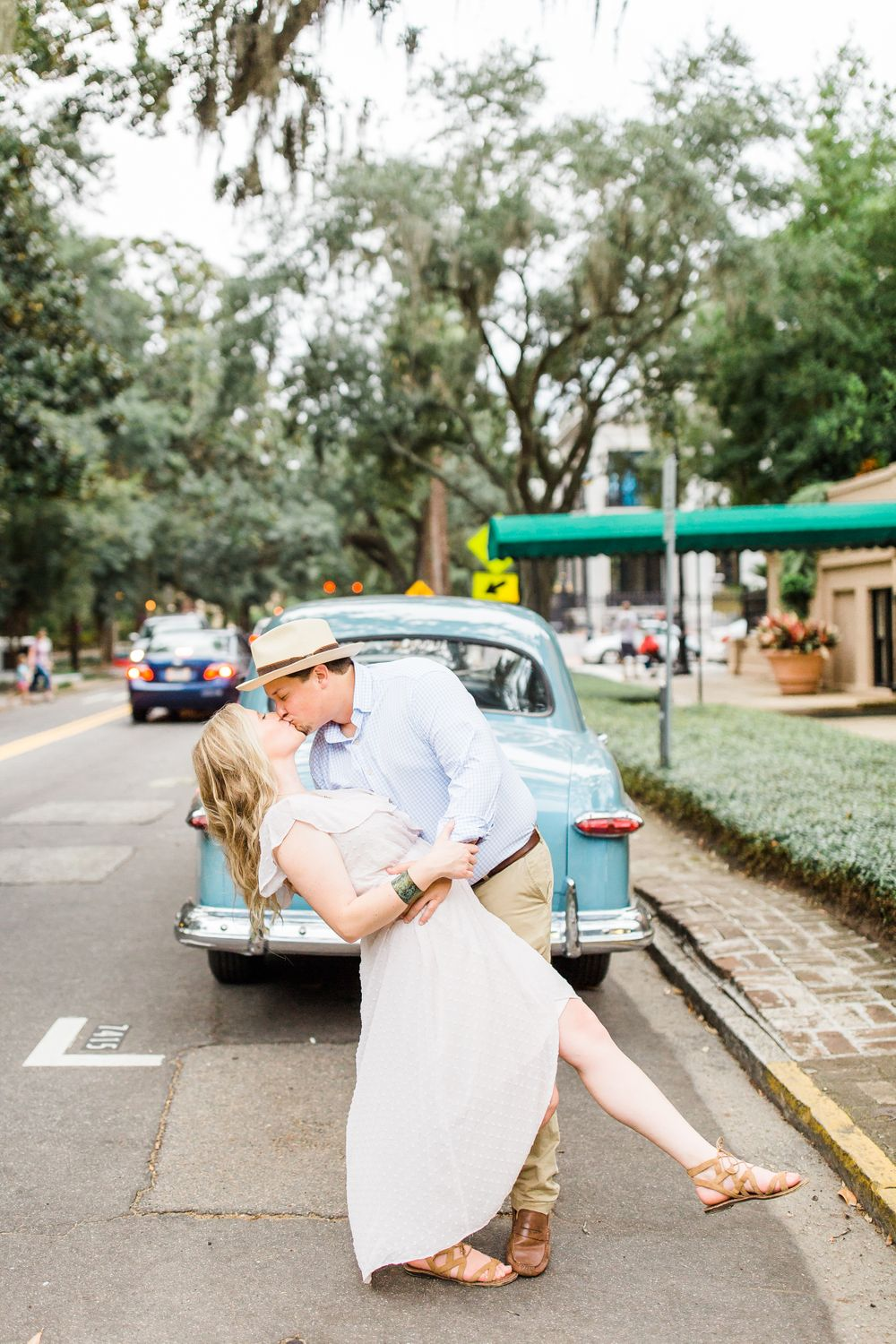 downtown savannah engagement session with couple kissing in front of an old car