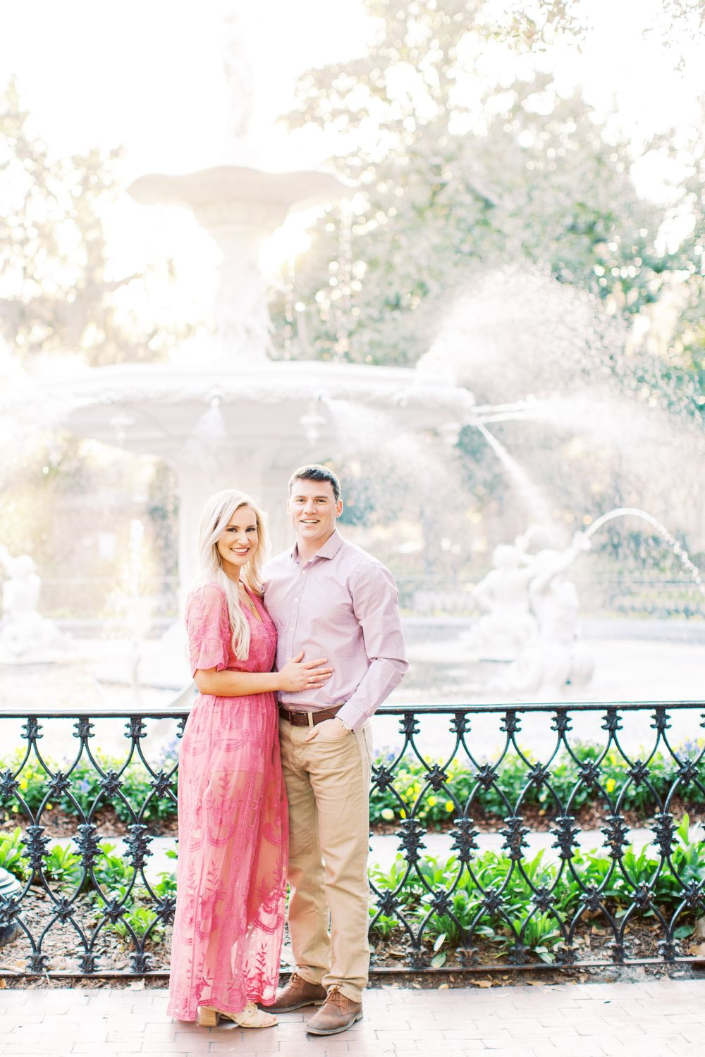 man and woman stand close to each other and smile while standing in front of the fountain in forsyth park