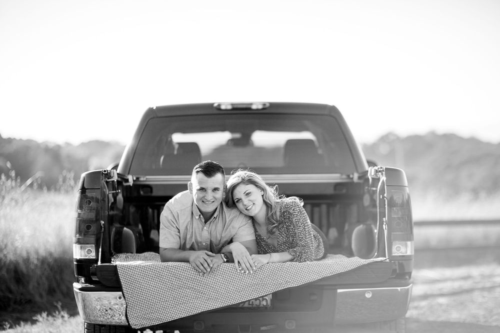 north sonoma mountain regional park engagement sunset couple laying in pick up truck smiling