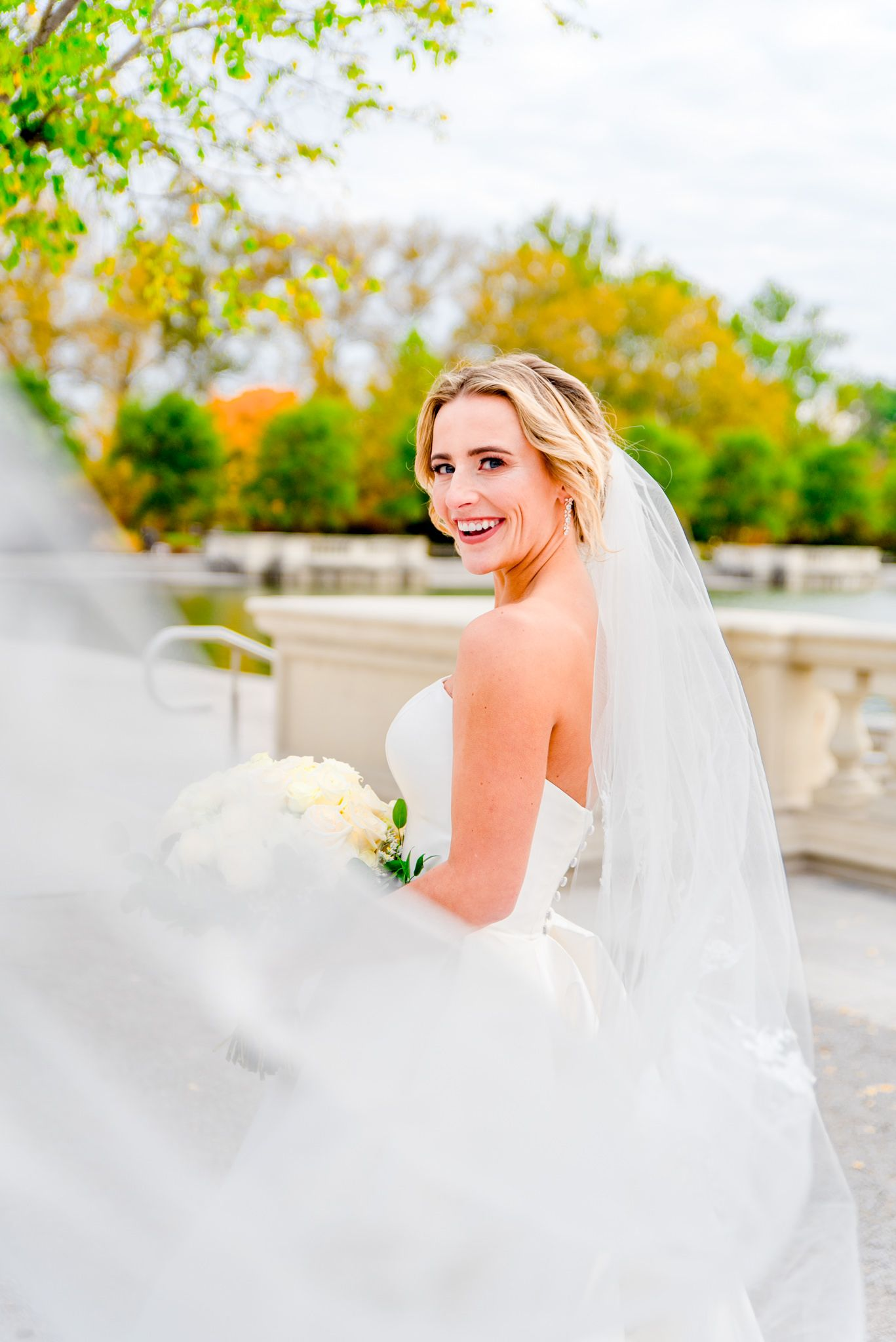 blonde bride with updo and long veil and white bouquet laughing at the camera for Forest Park STL wedding pictures