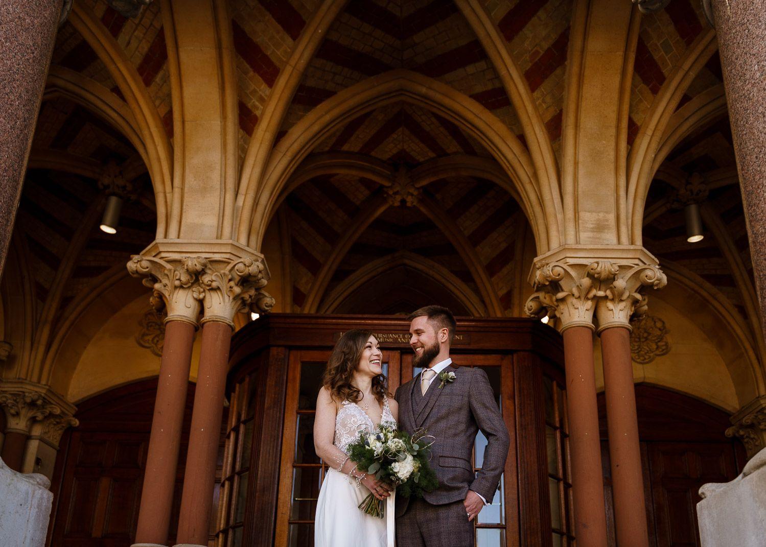 A newlywed bride and groom stand together under the grand arches of Winchester Guildhall after their Hampshire wedding.