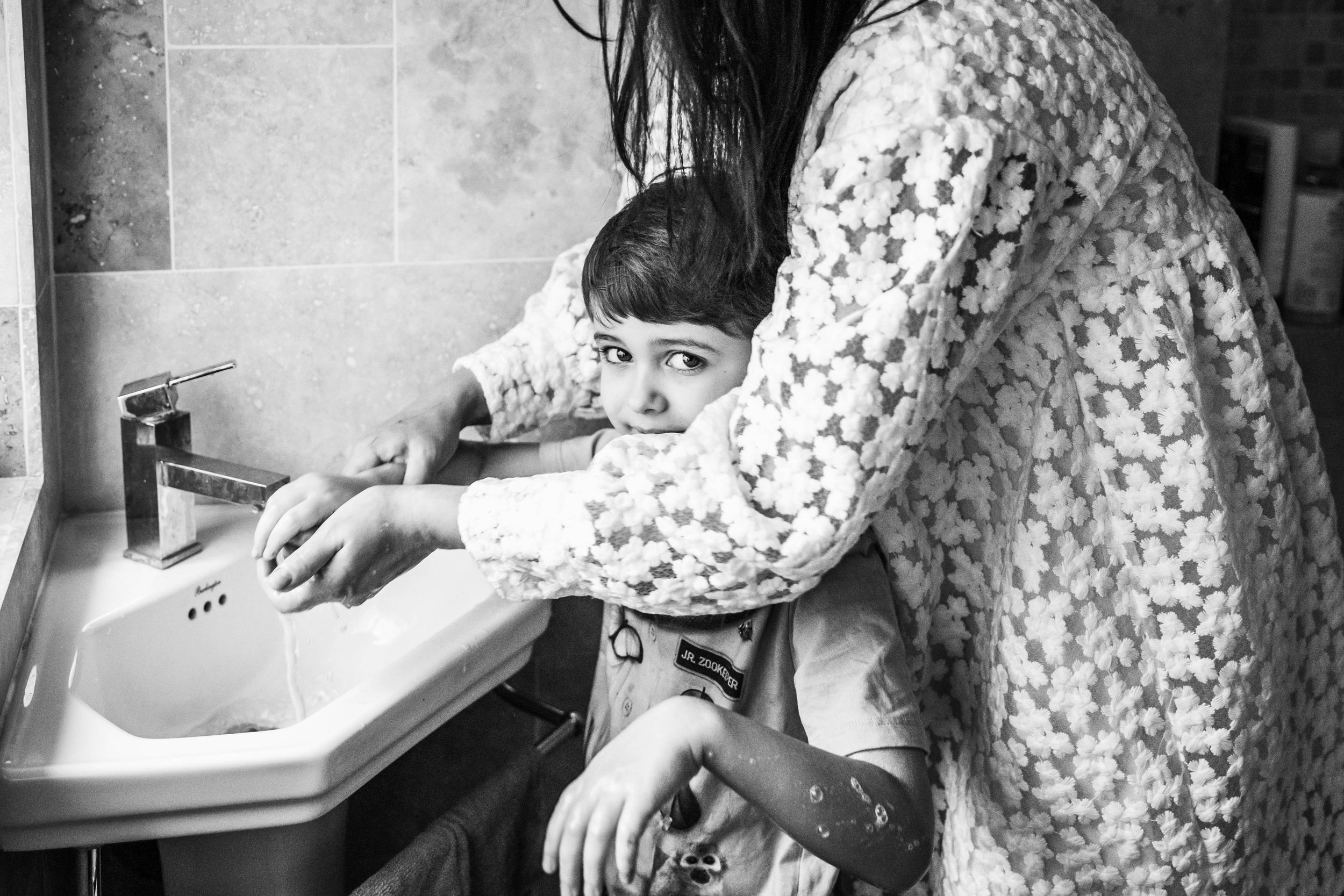 mum cleaning boy hands in bathroom black and white