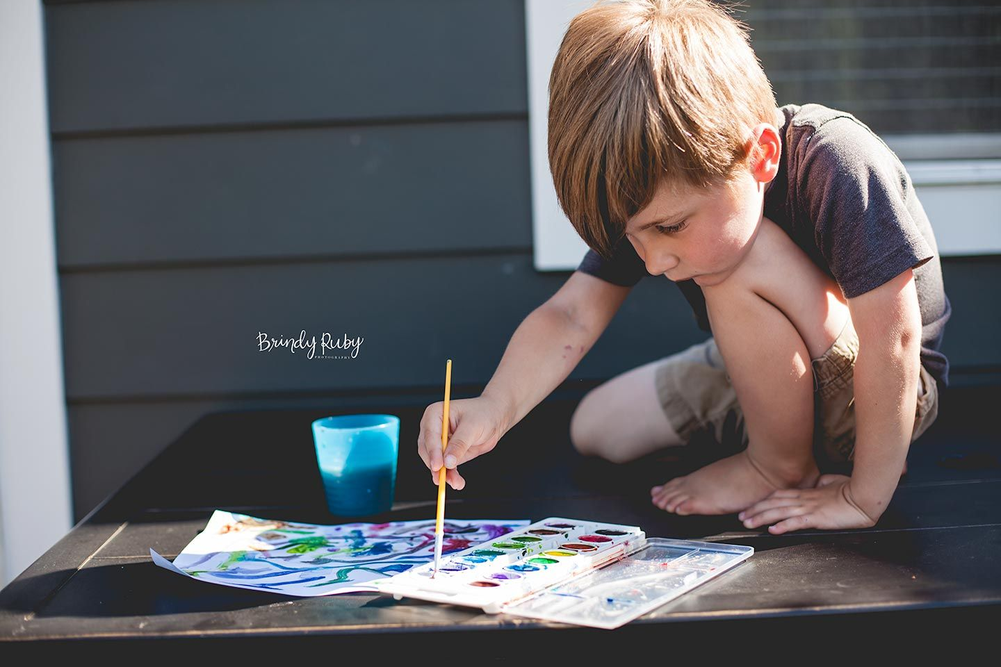 Young boy painting a watercolor painting