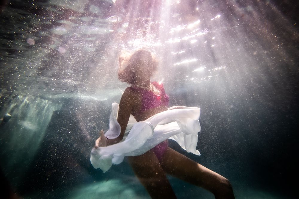 A silhouette of a woman underwater wearing a floating white skirt