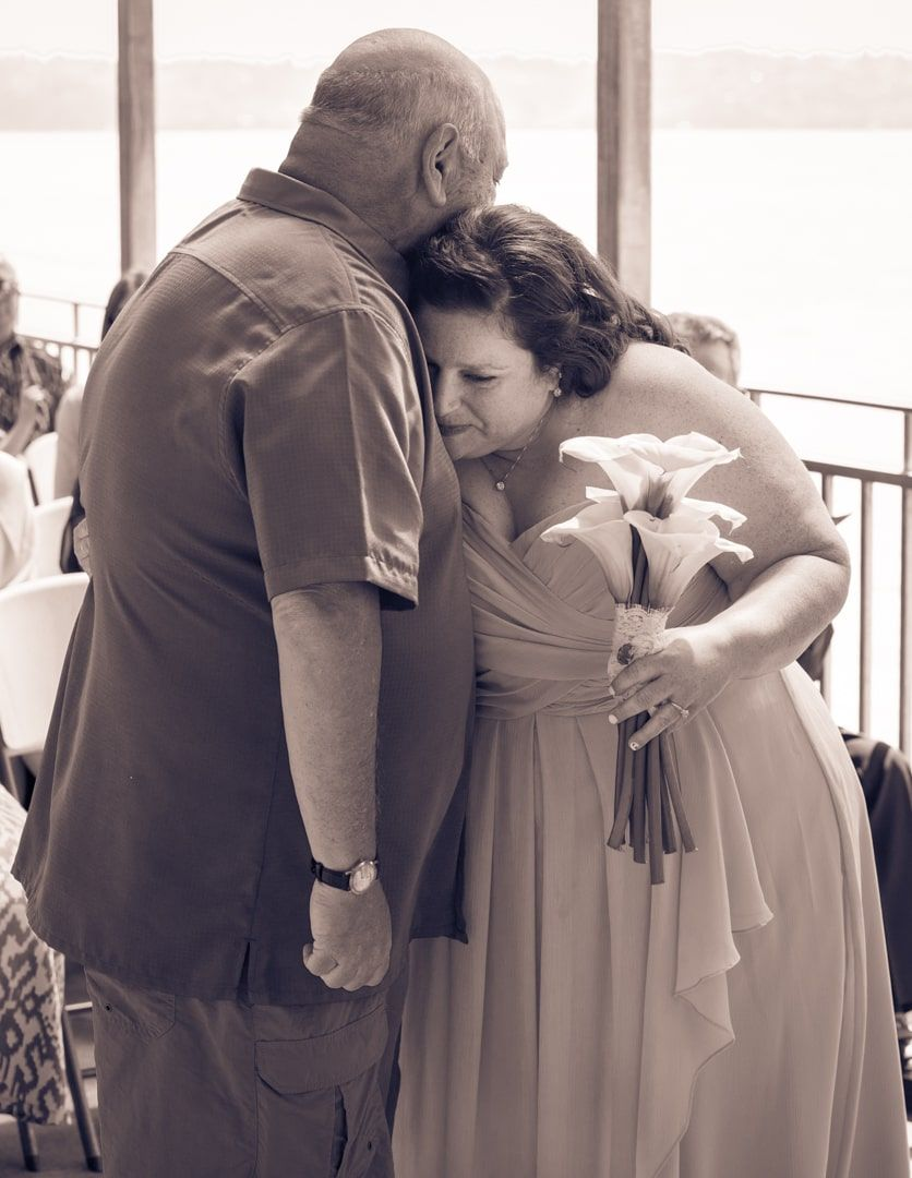 black and white sepia of bride and father hugging before he giver her away during wedding at brownspoint, wa