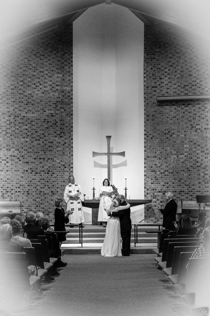 black and white of bride and groom hugging during ceremony at United Methodist Church in Puyallup, WA