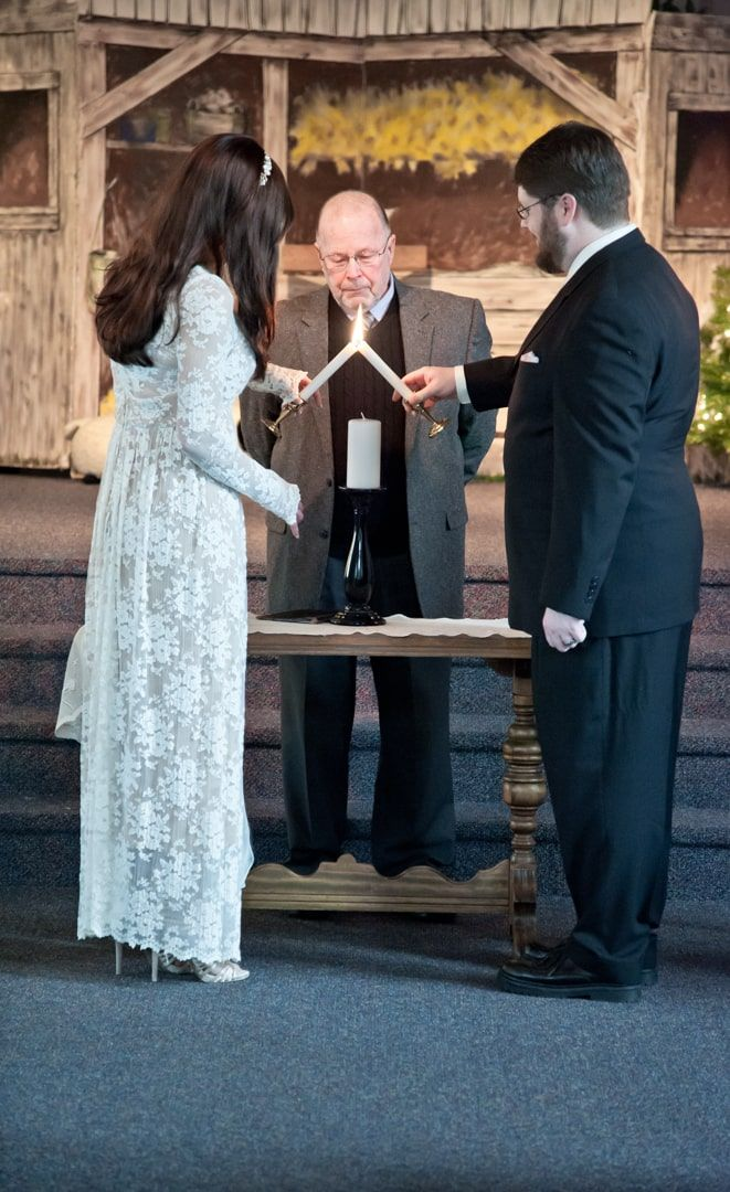 bride and groom lighting candle during Christmas wedding ceremony in west seattle