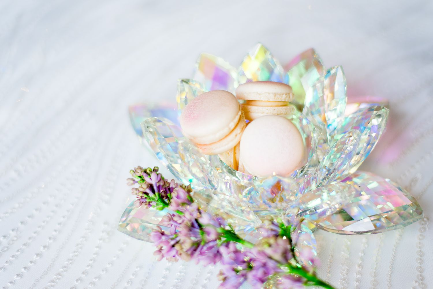 iridescent crystal bowl full of pink glitter macarons on top of sequin wedding dress with purple lilac