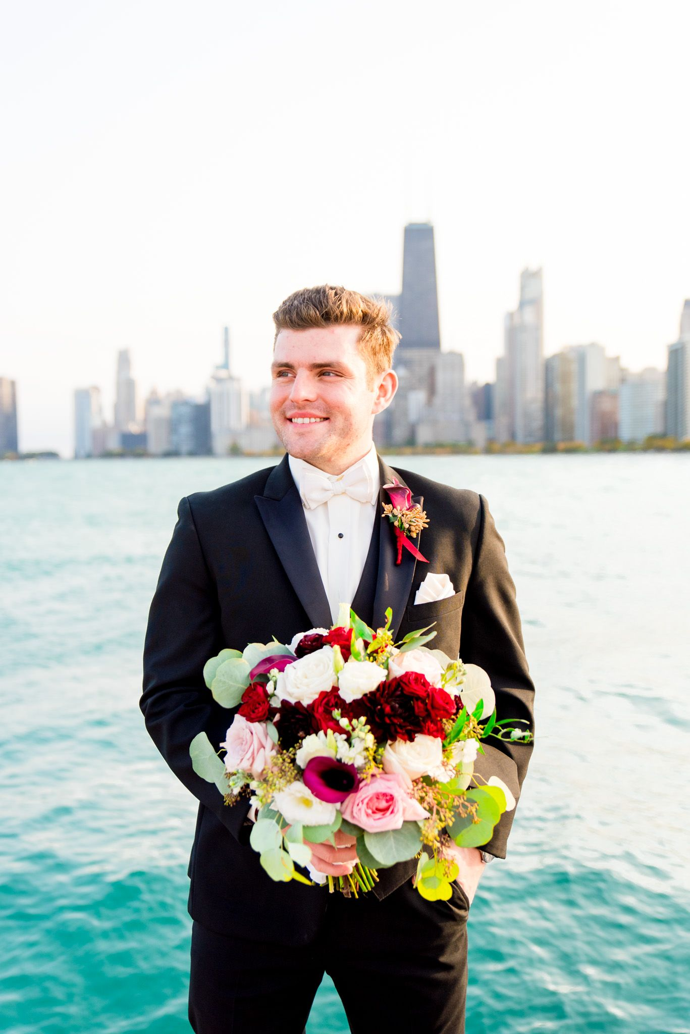 groom in black suit smiles in front of Lake Michigan holding red and blush bouquet for Chicago wedding pictures
