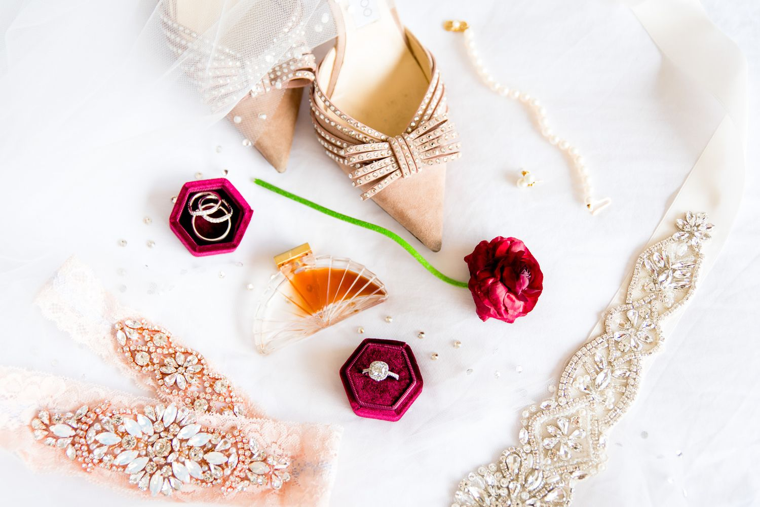 red and blush wedding details in a flat lay