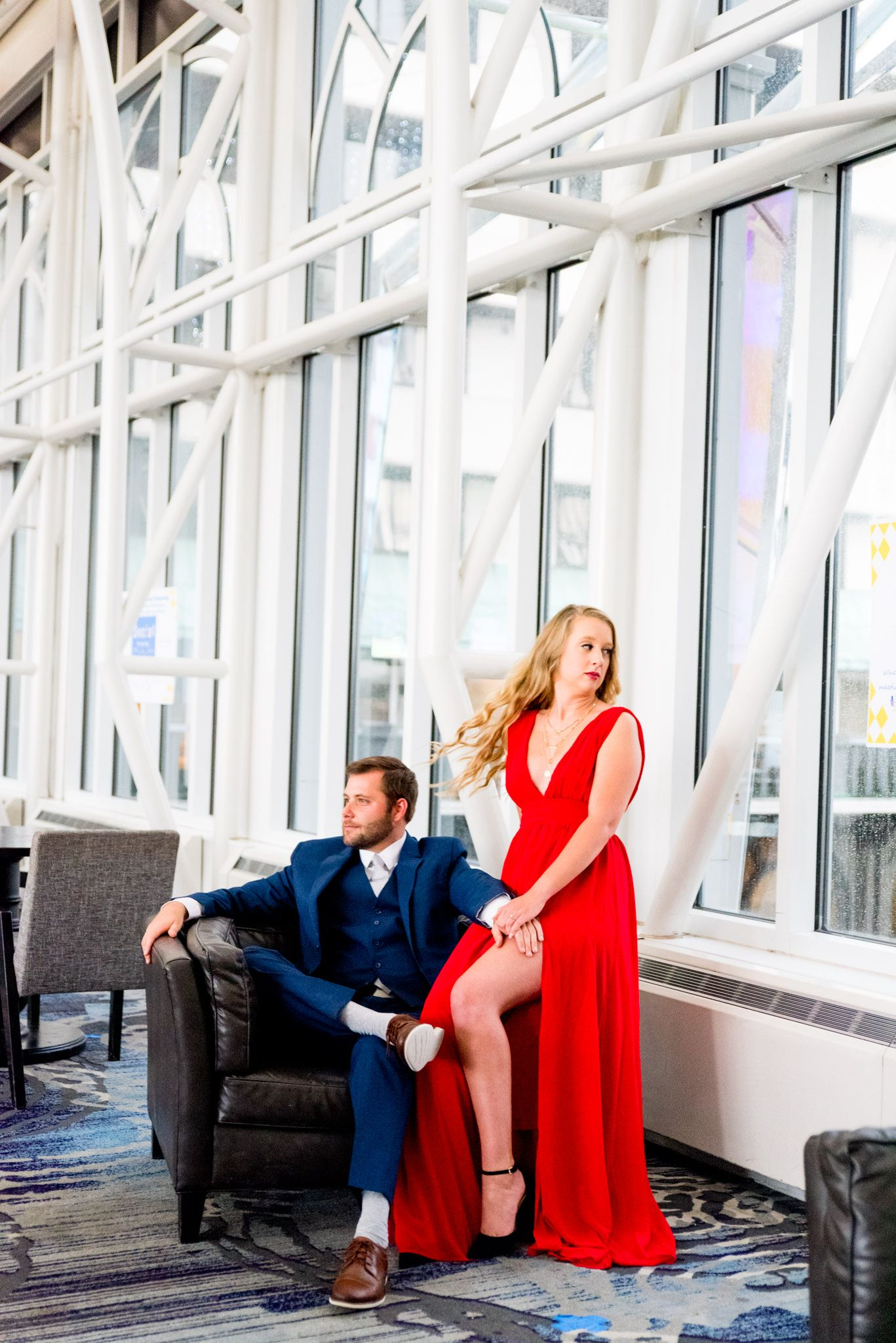 blonde woman in red dress sitting with fiance in navy suit at Galt House Hotel engagement pictures