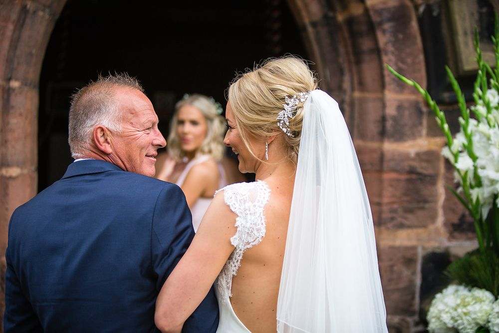 Father of the bride looks lovingly into his daughters eyes whilst being watched by a bridesmaid at a wedding in Cheshire