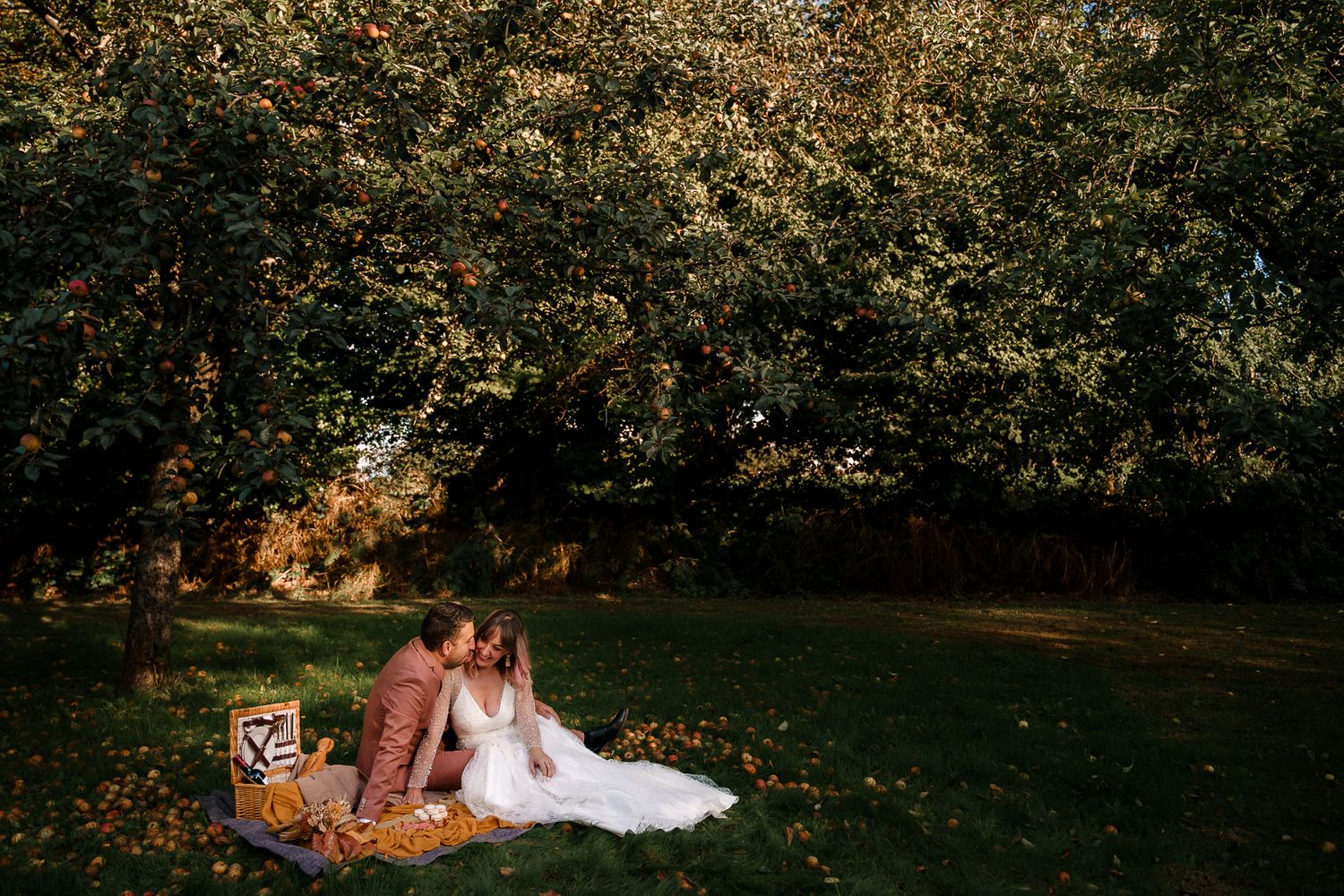 A bride and groom snuggle up together on a blanket with a picnic in a French orchard surrounded by golden fallen apples.