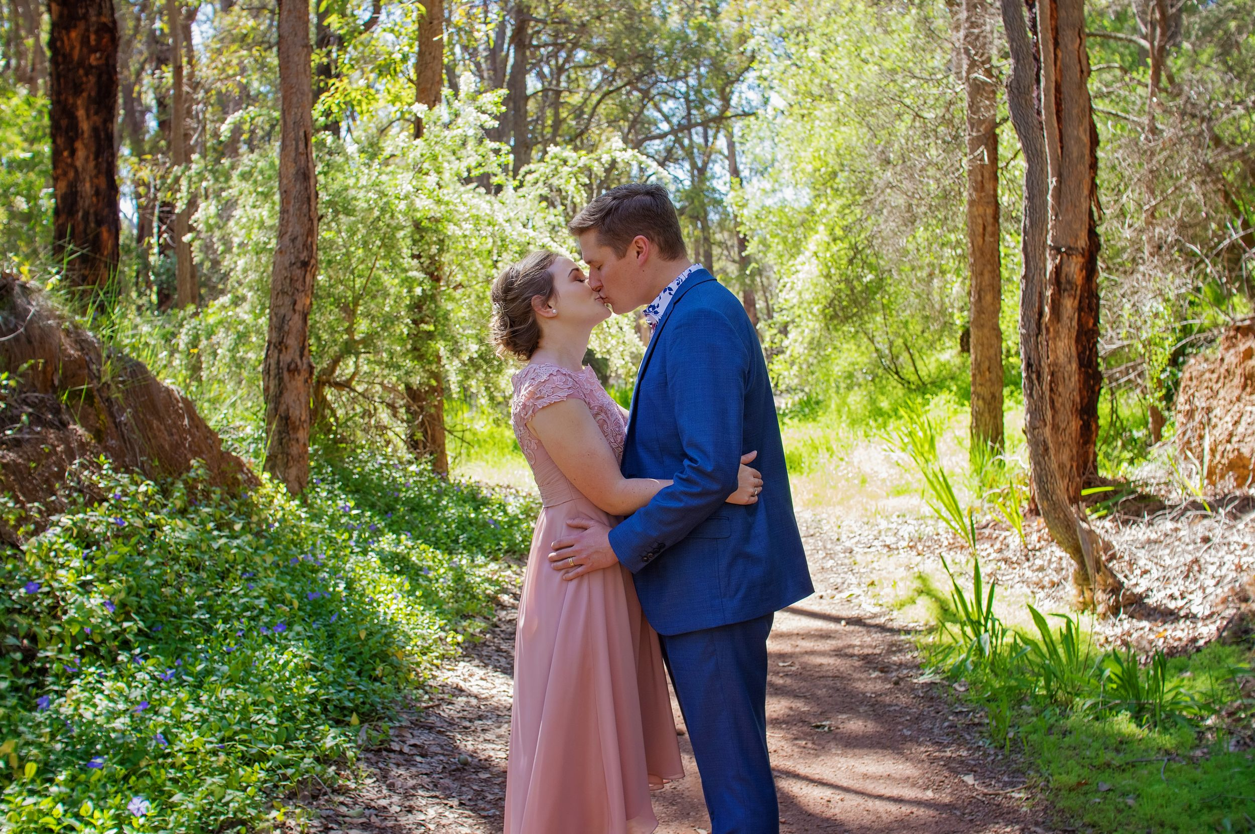 bride and groom wearing pink and navy kissing in forest