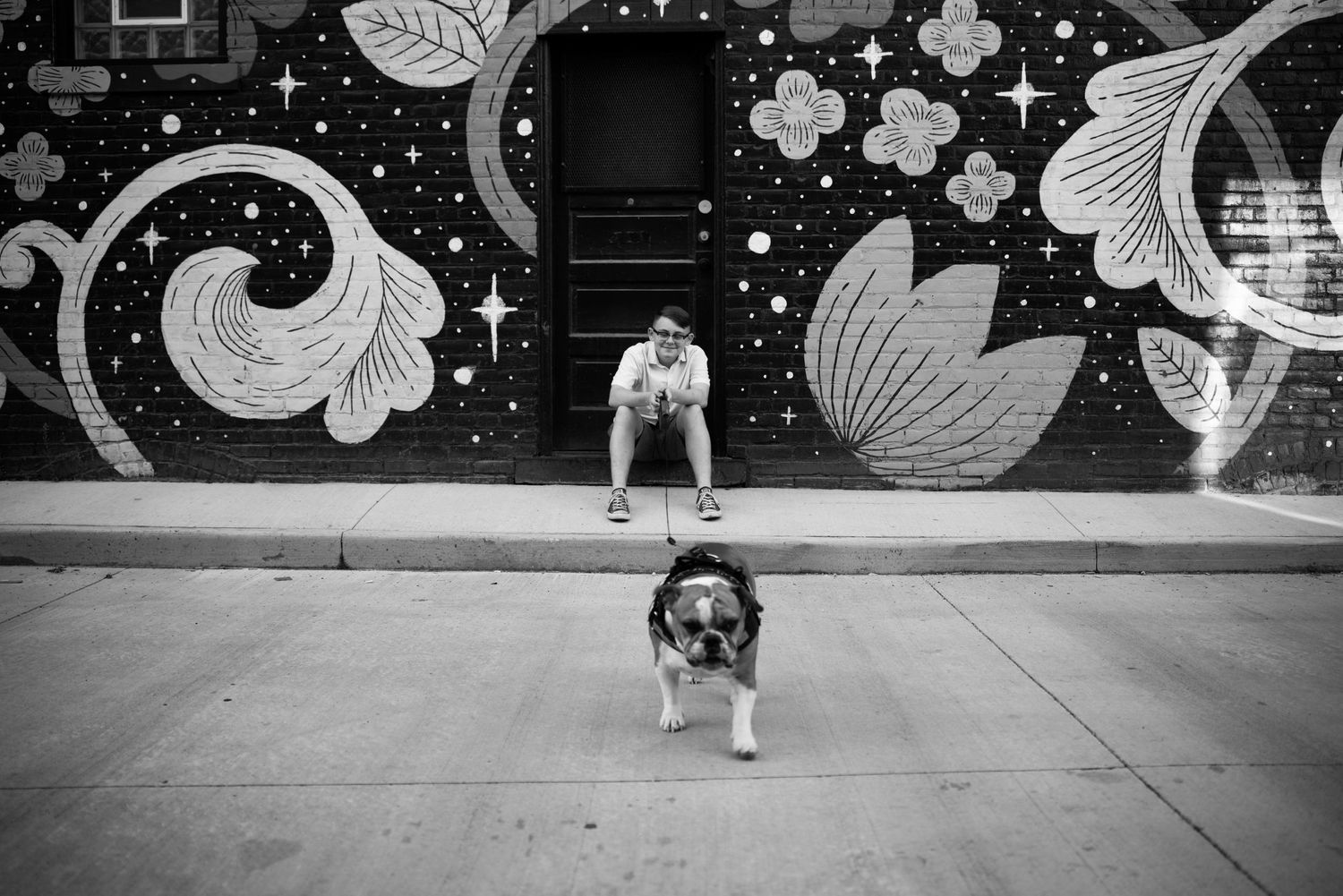 senior photo with dog in front of Gordon Square mural