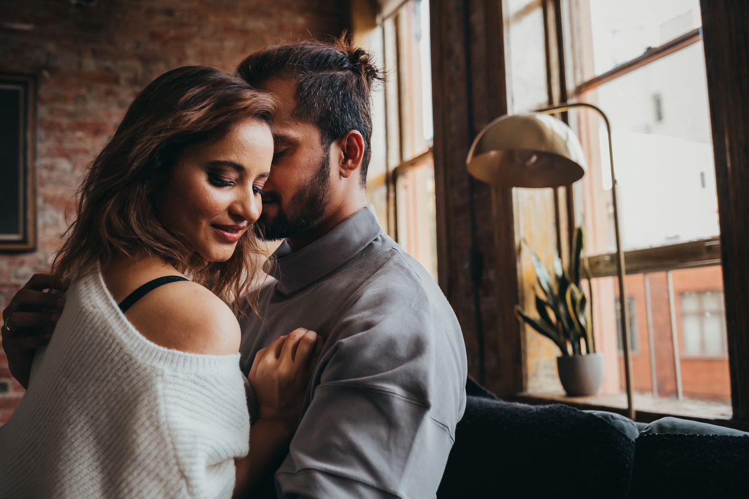 man whispers in womans ear romantically at loft in seattle for couples photography, Issaquah WA by Shutterbabe Snaphots