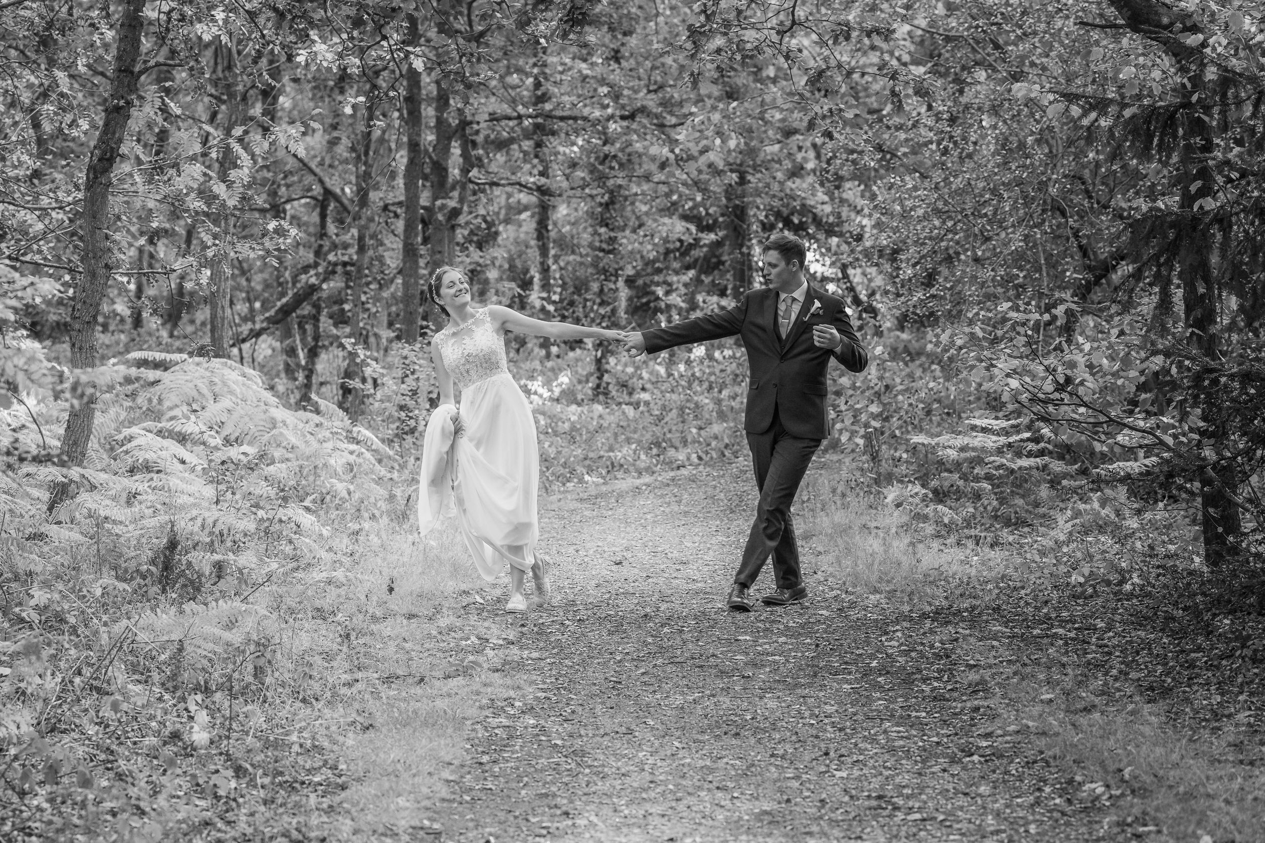 Bride and groom walking and dancing through the forrest