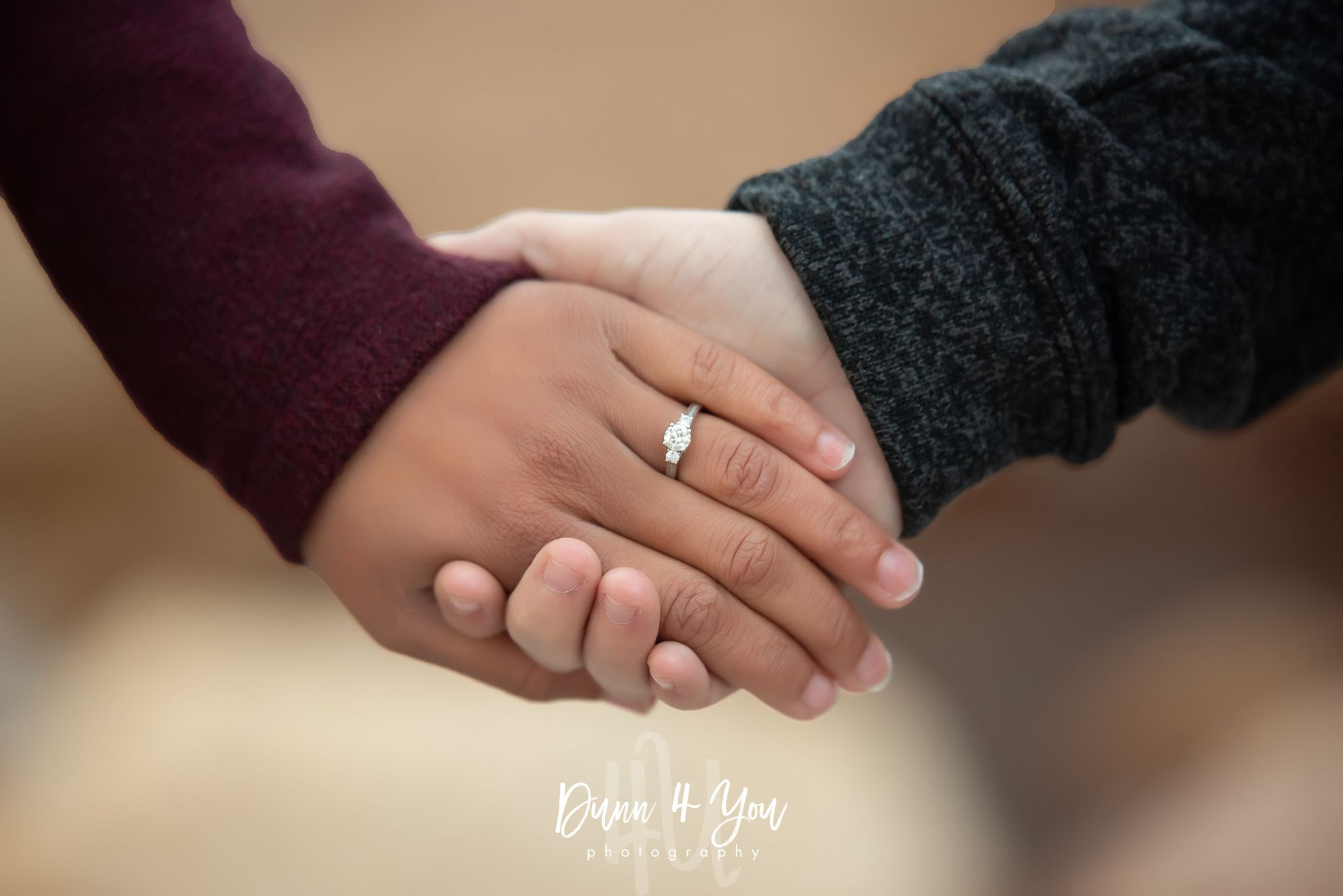 A couple's hands being held to show off engagement ring