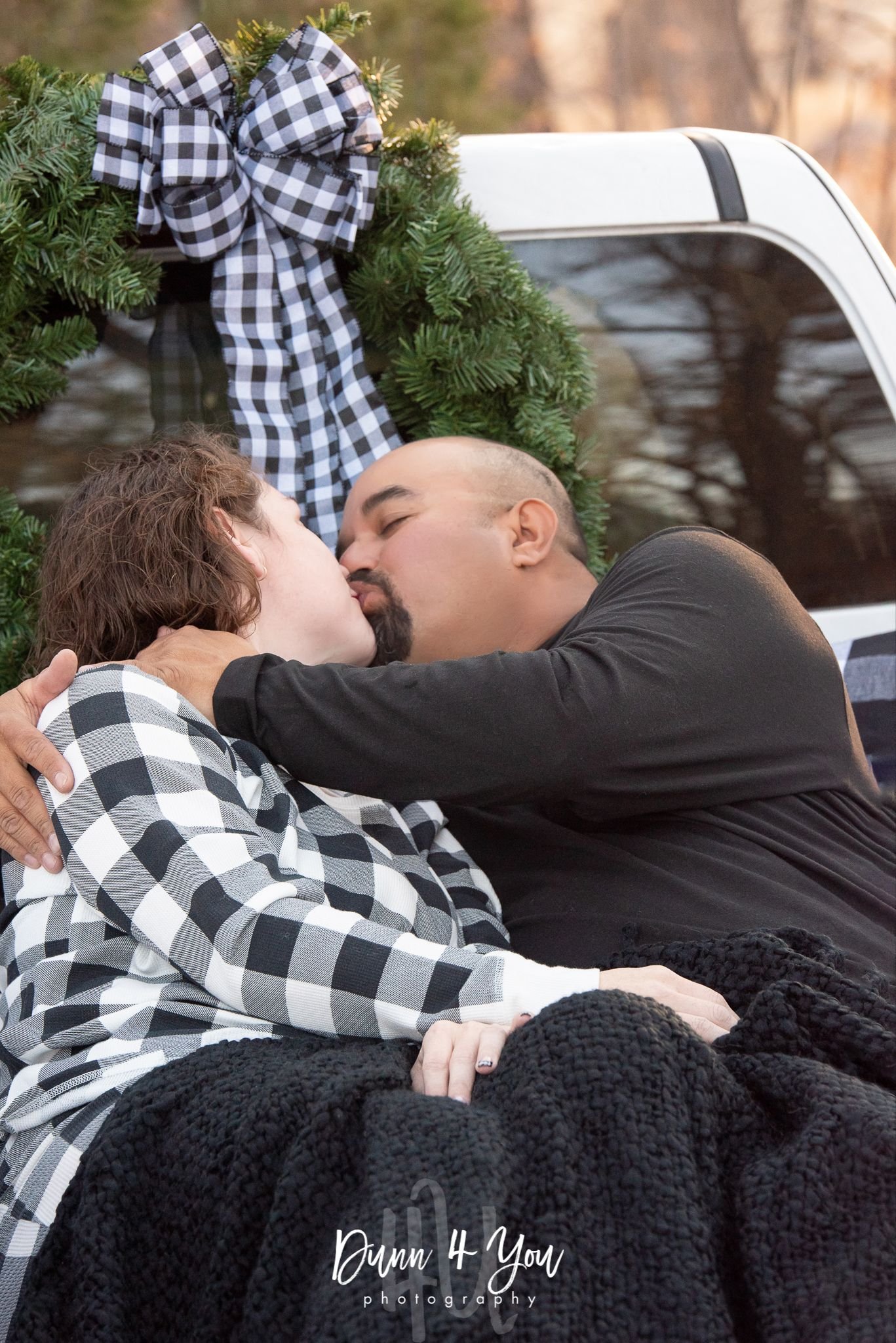 Couple shares a kiss for Christmas in buffalo plaid theme.