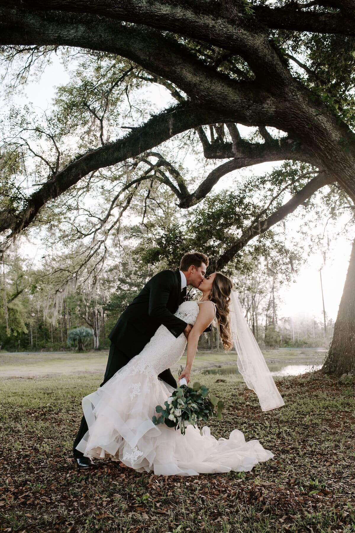 small Florida wedding newlywed groom dipping his bride under a large Florida tree. Audrey Darke Photography.