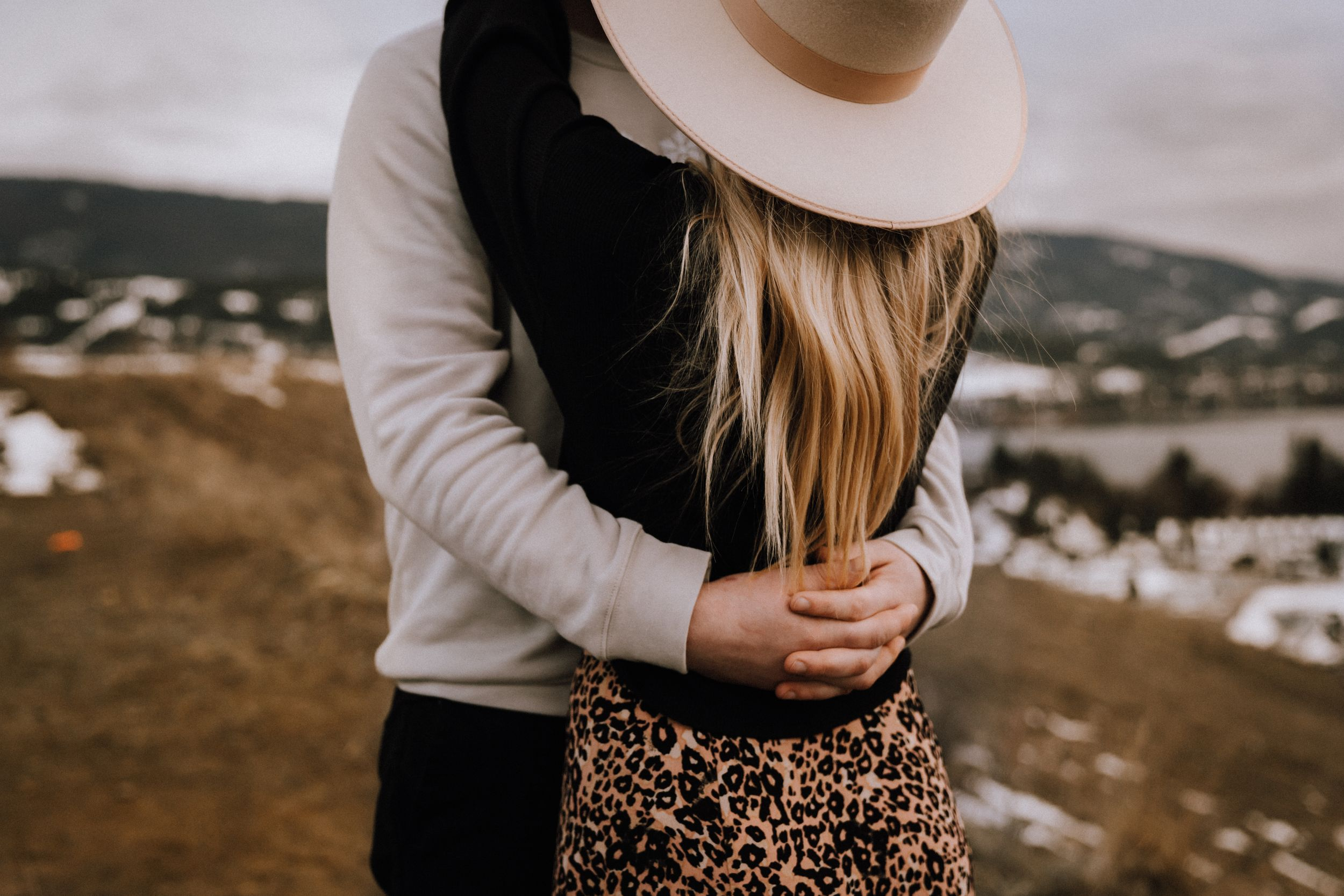 Couple embracing with mountains in background taken by Anna Kova Photography