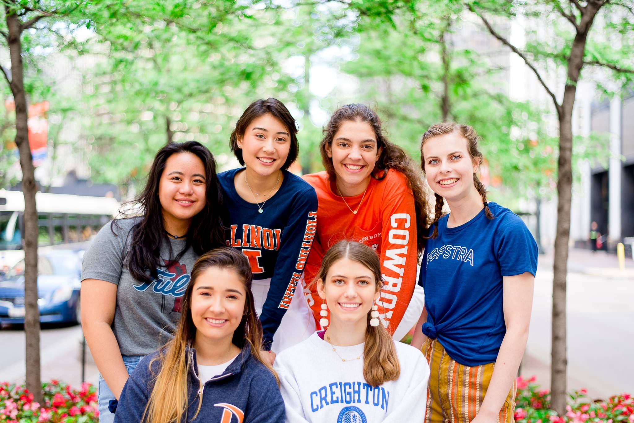 six girls in college t-shirts smiling for Chicago senior pictures in downtown Chicago