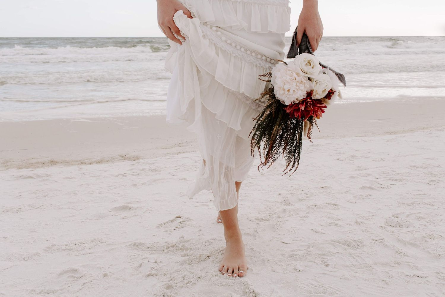 woman walking on the beach holding up her dress and flowers during her 30A elopement