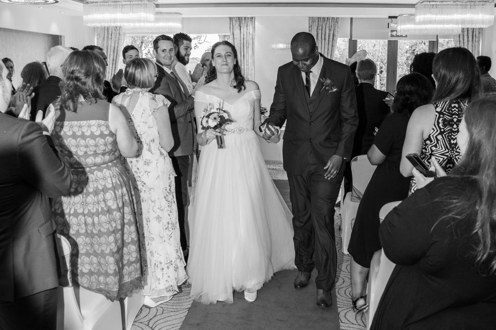 bride and groom walking up the aisle at Bromley Court Hotel