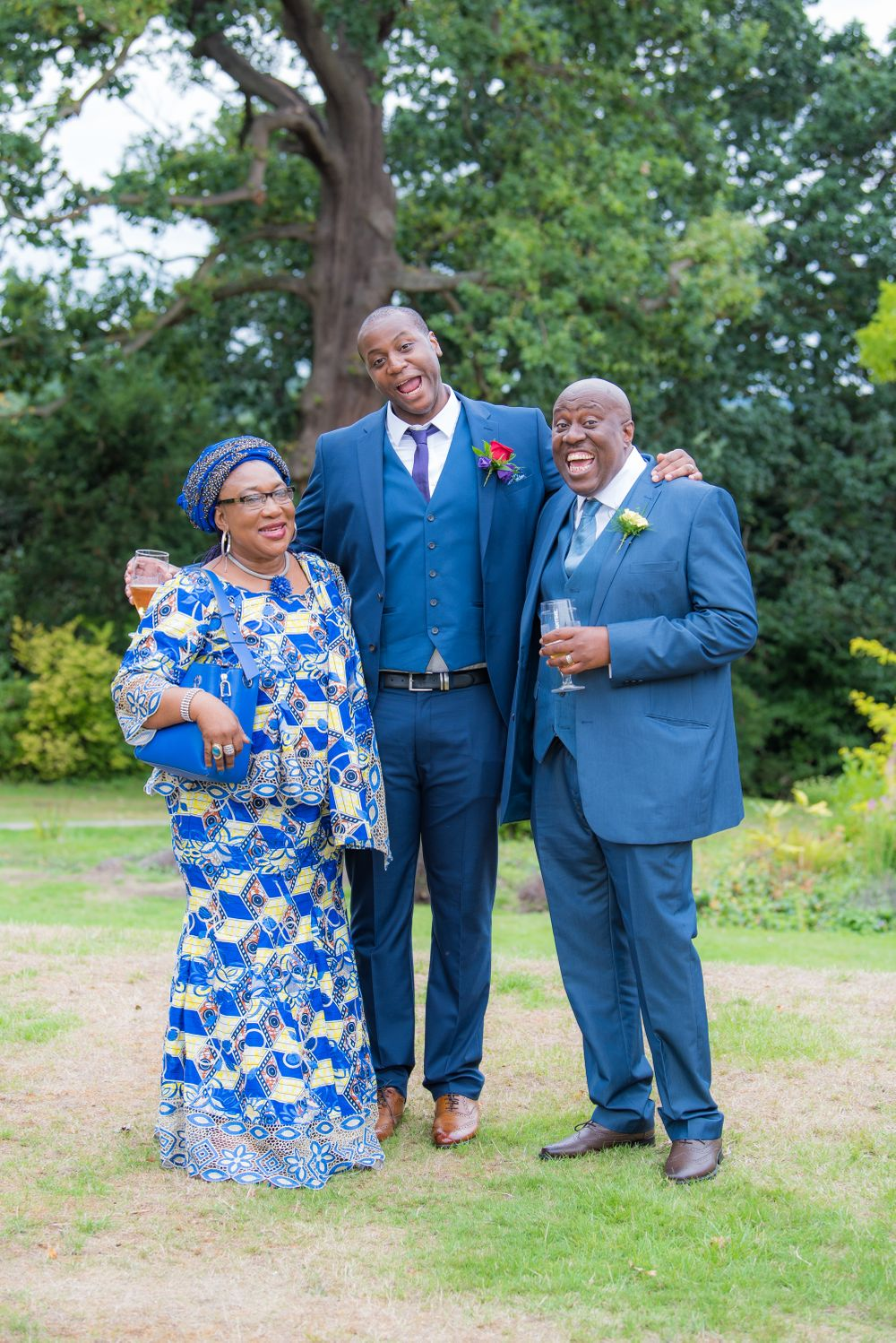 groom with parents on the lawn at Bromley Court Hotel