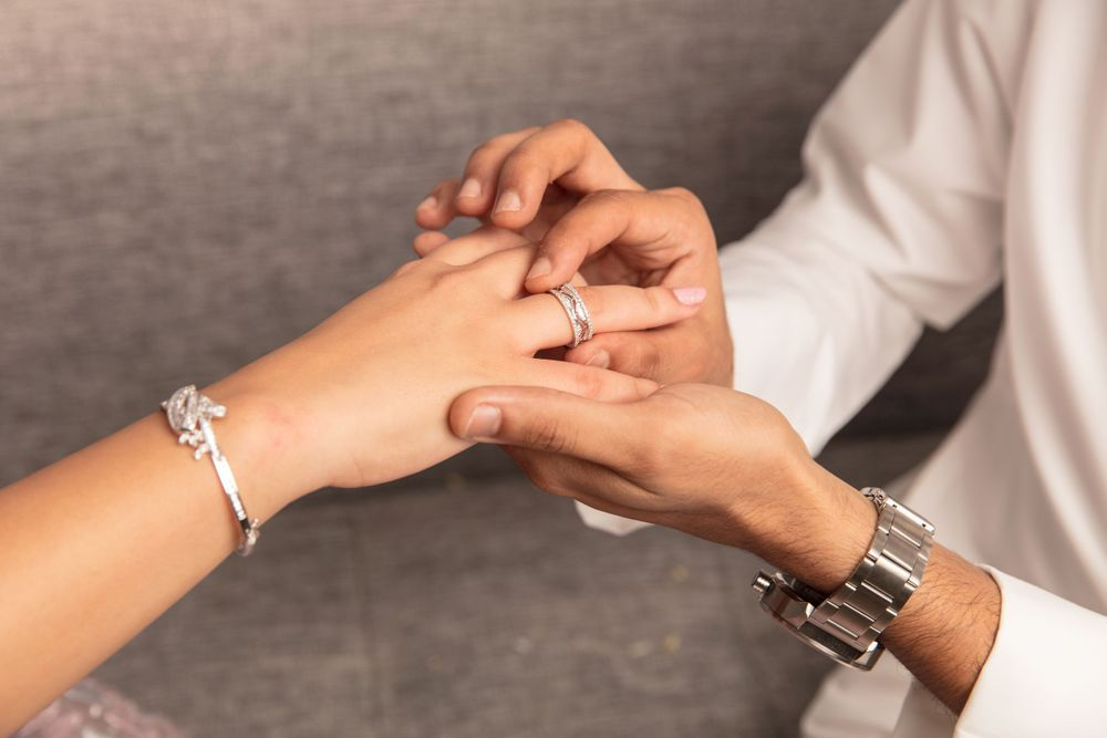 close up of hands during exchange of wedding rings