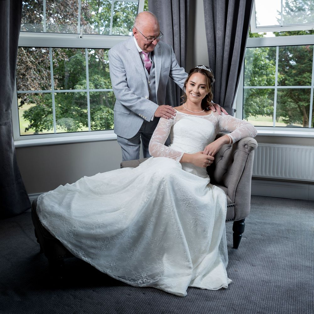 Bride sat in front of windows lokking at the camera whilst her dad stands to her side looking down at her.