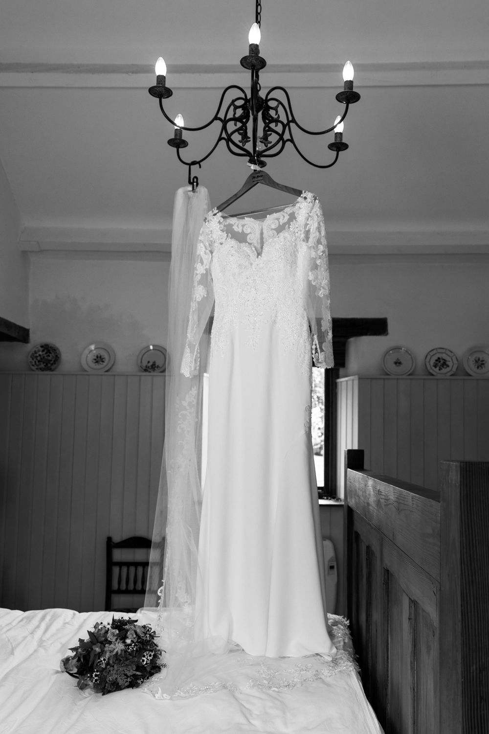 Black and white photo of wedding dress hanging from ceiling light.