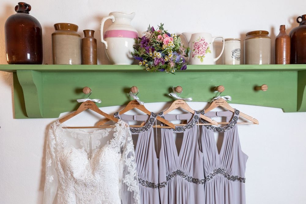 wedding dress and lilac bridesmaids dresses hang on a green shelf.