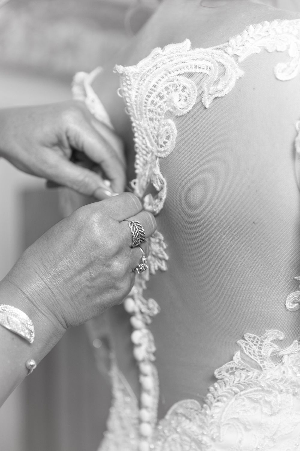 Close up black and white image of hands doing up the back of a delicate wedding dress.