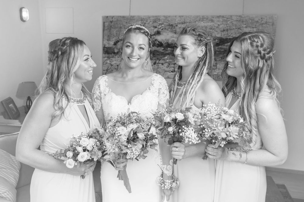 Black and white image of bridesmaids stood next to, and looking at, the bride, who is looking at the camera.