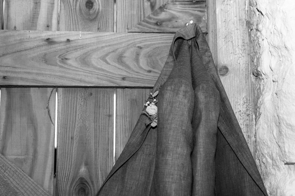 Black and white image of a suit jacket hanging on the back of a bar door.