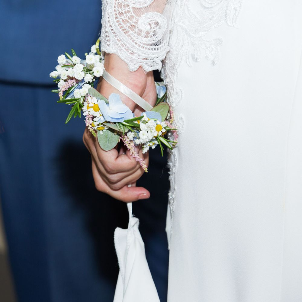 Image of bride's hand holding dress and wearing a floral bracelet.
