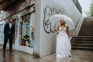 Rainy downtown Toronto wedding first look where bride is waiting around the corner for her groom with clear umbrella