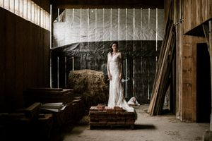 Toronto moody bridal portrait of tattooed bride posing in barn with light beams coming through.