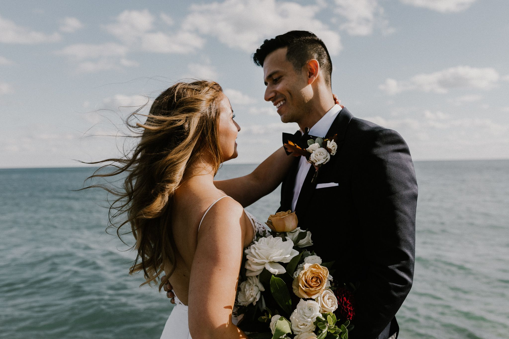 Toronto Wedding couple by the sea at R.C. Harris Water Treatment plan with the wind in their hair and bouquet.