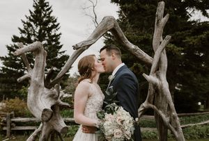 PEI wedding at Green Island Getaways with bride and groom kissing under driftwood wedding arch.