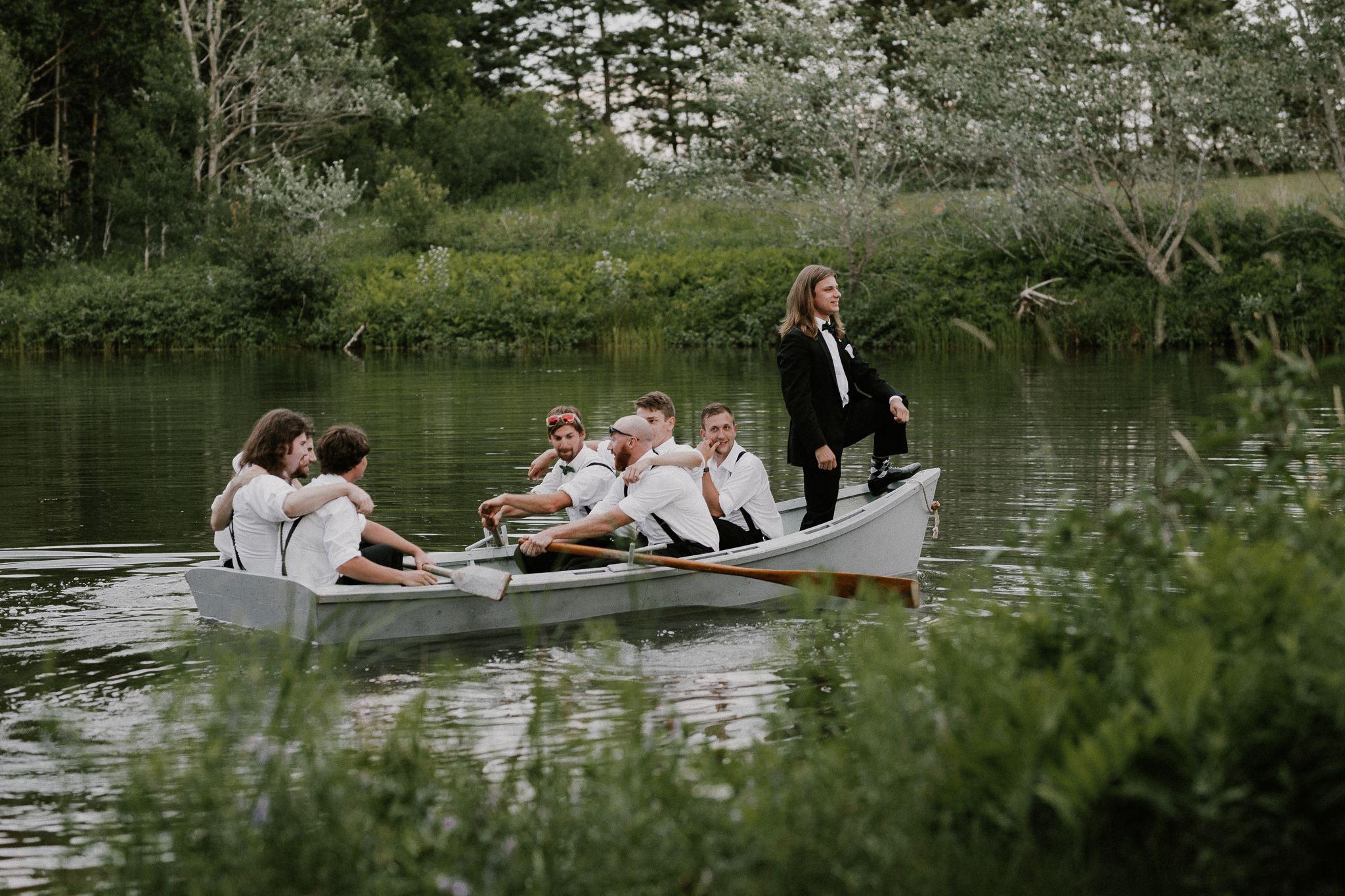 PEI groom and wedding party in a boat at Hazelbrook Homestead drinking No Boats on Sunday.