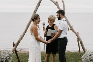 PEI bride & groom with officiant smiling at each other during ceremony at Centre Le Goéland and driftwood arch.