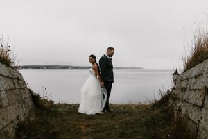 PEI wedding couple posing back to back at Victoria Park cannons on a rainy October PEI wedding.