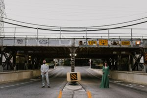 Downtown Toronto wedding couple in the middle of an underpass drinking and acting silly. Green wedding dress.