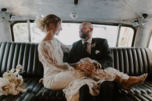 Boho minimalist Toronto wedding couple posing in vintage Airstream at Airship37. Rue de Seine wedding dress.
