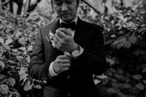 Black and white photo of Toronto groom touching cuff links at DVP parks.